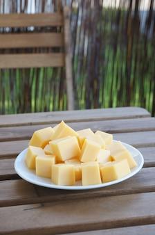 Close up vertical de blocos de queijo gouda em um prato branco sobre uma superfície de madeira