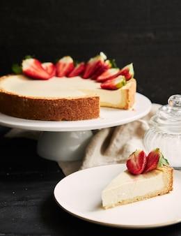 Close up vertical de cheesecake de morango em prato branco