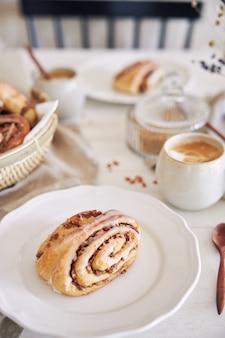 Close up vertical de deliciosos caracóis nut com cappuccino de café na mesa de madeira branca