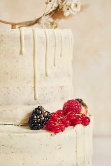 Close up vertical de um delicioso bolo de casamento decorado com frutas frescas e bagas