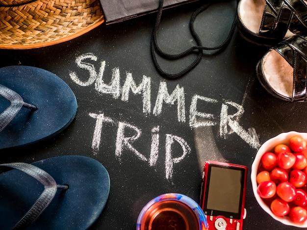 Close-up viagem de verão escrito texto no quadro preto com acessórios de viagem de senhora