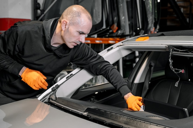 Close up, vidros do carro, consertando e reparando um pára-brisa. processo de substituição do pára-brisa de um carro em um serviço de garagem. limpando um painel.
