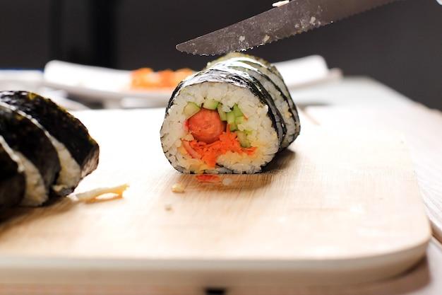 Close up view processo de preparação de rolling sushi / gimbap / kimbap. nori e arroz branco. as mãos do chef tocam o arroz em rolo. chef cortando kimbop ou cozinhando sushi com faca afiada