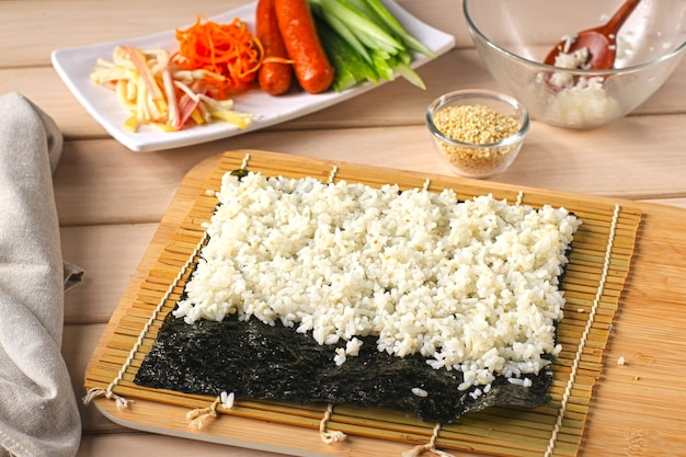 Close up view processo de preparação de rolling sushi / gimbap / kimbap. nori e arroz branco. preparando arroz acima da alga nori. processo de cozimento na cozinha
