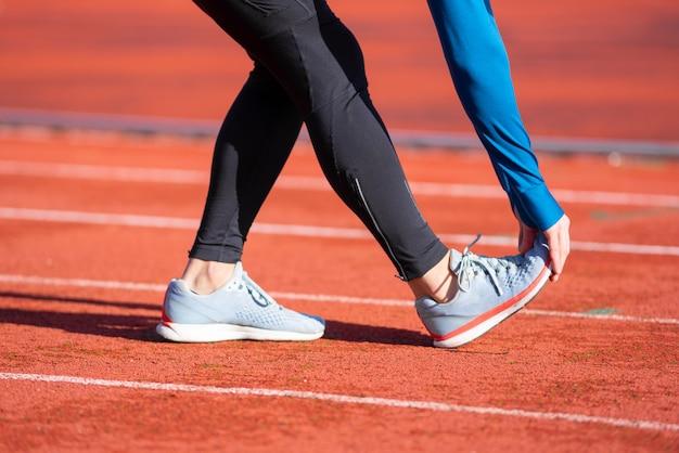Close-up vista, atleta, estendendo-se em uma pista de corrida.