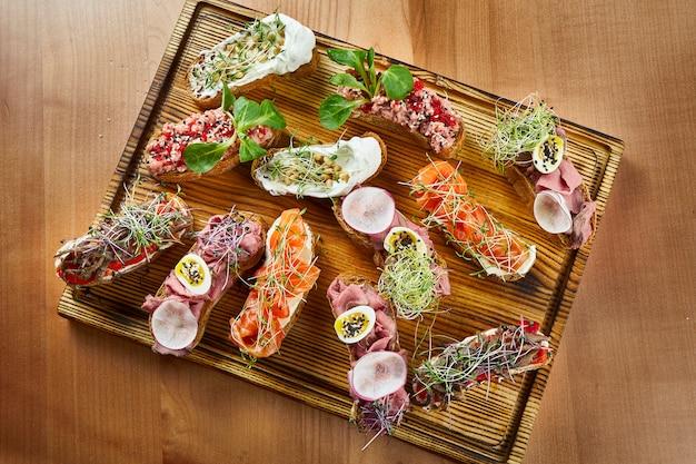 Close-up vista bruschetta deliciosa sortida com salmão, carne e tomate na superfície de madeira