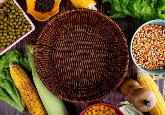 Close-up vista da cesta vazia com grãos de milho sementes ervilhas verdes pimenta preta na mesa de madeira