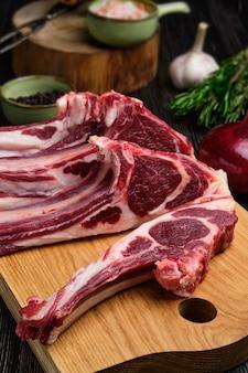 Close-up vista da costela de carneiro crua fresca na placa de corte