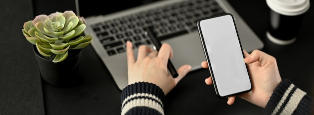 Close-up vista da empresária trabalhando com tablet digital enquanto olha no smartphone
