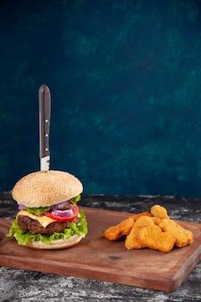 Close-up vista da faca no saboroso sanduíche de carne e nuggets de frango na placa de madeira na superfície azul escuro