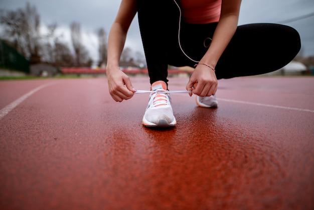 Close-up vista da garota fitness se preparando para exercitar amarrar sapatos na pista de atletismo.