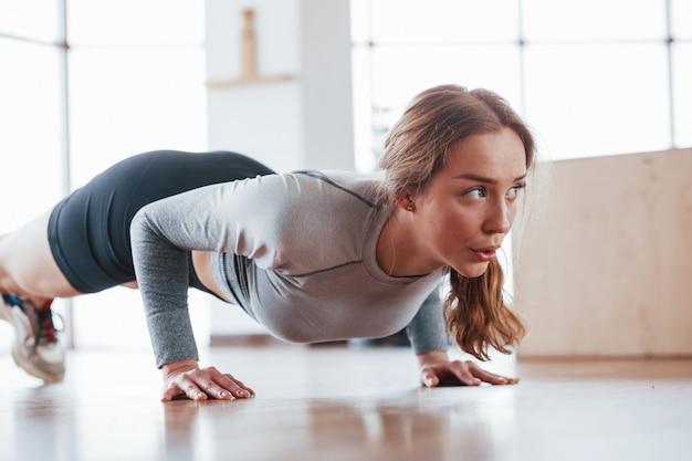 Close-up vista da garota que faz alguns exercícios. jovem esportiva fazendo exercícios na academia pela manhã