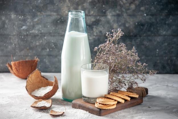 Close-up vista da garrafa de vidro e do copo cheio de leite na bandeja de flores de madeira em fundo escuro