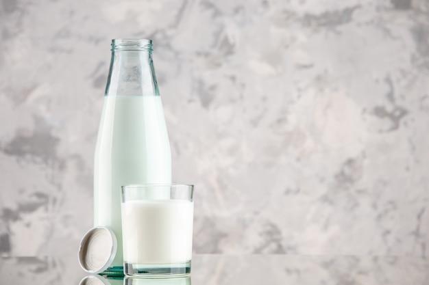 Close-up vista da garrafa de vidro e do copo com tampa de leite em um fundo de cores pastel com espaço livre