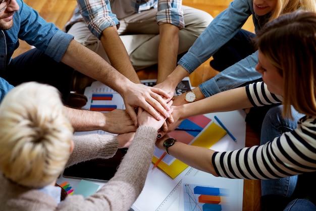Close-up vista da jovem equipe motivada de empresários juntando as mãos entre eles enquanto está sentado no chão do escritório.