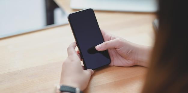 Close-up vista da jovem fêmea segurando o smartphone na mesa de madeira