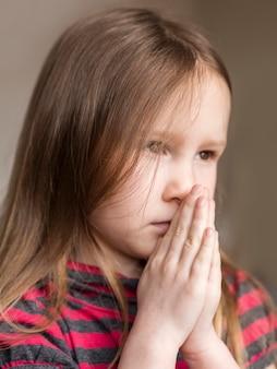 Close-up vista da linda garotinha rezando