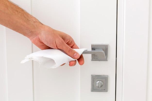 Close-up vista da mão do homem usando lenço umedecido antibacteriano para desinfetar a ligação da porta do quarto em casa.