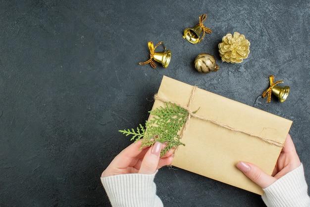 Close-up vista da mão segurando a caixa de presente e acessórios de decoração em fundo escuro