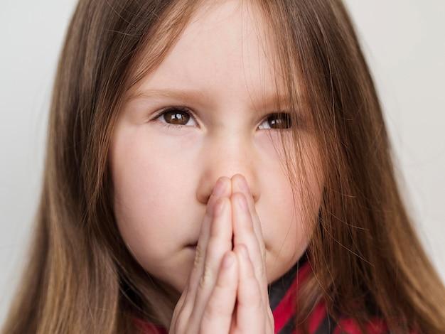 Close-up vista da menina bonitinha rezando