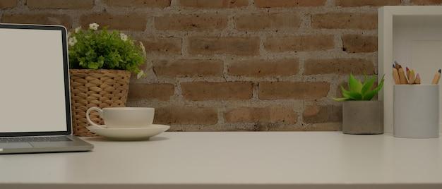 Close-up vista da mesa de escritório em casa com espaço de cópia, simulação de laptop, suprimentos e decorações na sala de estar