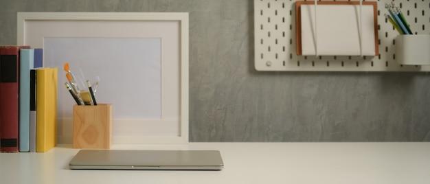 Close-up vista da mesa de estudo com laptop, papelaria, livros, decorações e espaço de cópia na sala de estar