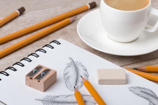 Close-up vista da mesa do artista ou designer. lápis, apontador e borracha no livro de desenho com penas desenhadas à mão