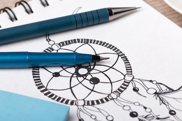 Close-up vista da mesa do artista ou designer. lápis, delineador fino e borracha no caderno de desenho com o apanhador de sonhos desenhado à mão
