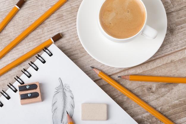 Close-up vista da mesa do artista ou designer. xícara de café, lápis, apontador e borracha no caderno de desenho com penas desenhadas à mão
