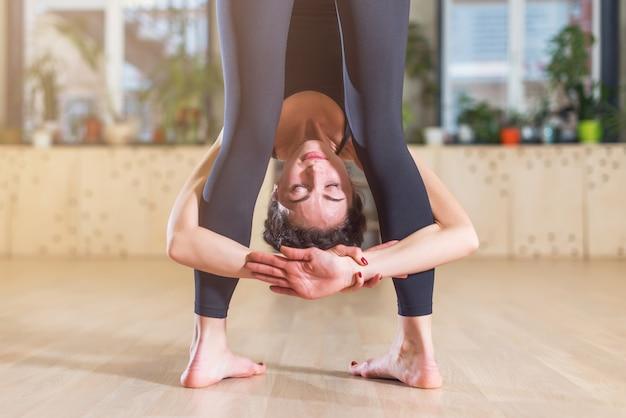 Close-up vista da mulher iogue com a cabeça entre as pernas em pé, curvando-se para a frente, pose de ioga dentro de casa.