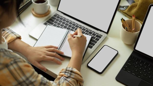 Close-up vista da mulher na mão da jaqueta scott, escrevendo no caderno em branco e trabalhando com o smartphone e o laptop no traçado de recorte da mesa