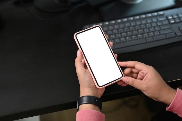 Close-up vista da mulher segurando o telefone móvel com tela em branco em seu local de trabalho. tela em branco para montagem de display gráfico.