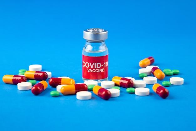 Close-up vista da vacina covid- em cápsulas de comprimidos de ampola médica em fundo azul escuro e suave