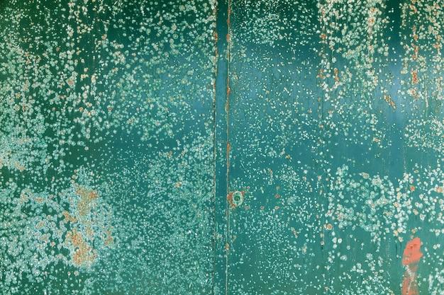 Close-up vista da velha placa enferrujada que está pendurada na parede do edifício.