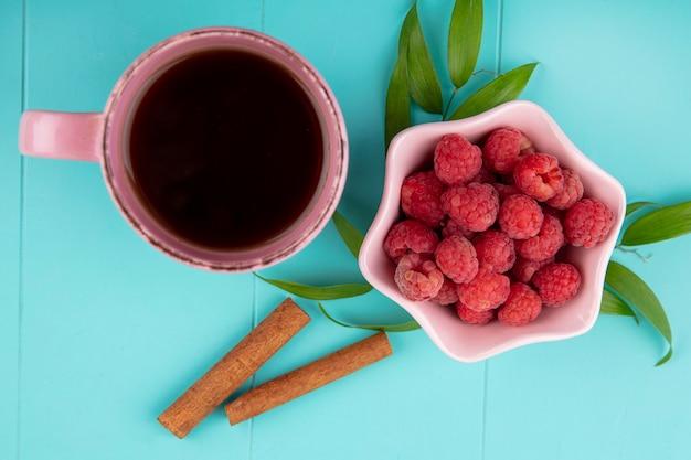Close-up vista da xícara de chá e tigela de framboesa com canela e folhas