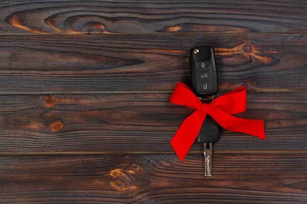Close-up vista das chaves do carro com laço vermelho como presente na madeira