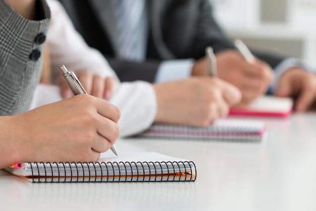 Close-up vista das mãos de alunos ou empresários escrevendo algo durante a conferência