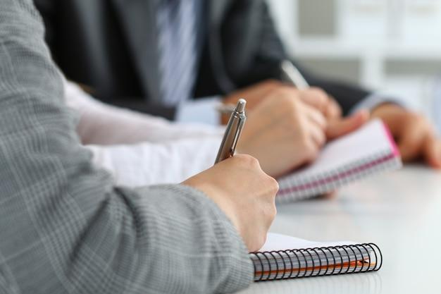 Close-up vista das mãos de estudantes ou empresários escrevendo algo durante a conferência. reunião de negócios, blog ou conceito de educação profissional