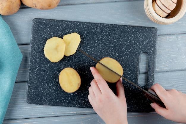 Close-up vista das mãos de mulher cortando batata com faca na tábua sobre fundo de madeira