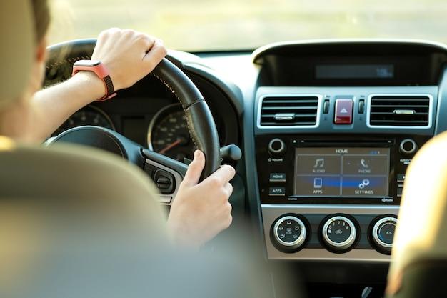 Close-up vista das mãos de mulher segurando o volante, dirigindo um carro na rua da cidade em dia ensolarado.