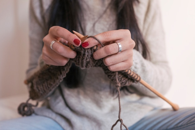 Close-up vista das mãos de mulher tricotando na cama. trabalhando em casa, em ambientes fechados