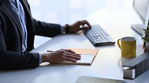 Close-up vista das mãos do empresário digitando no teclado ee escrevendo algo em seu livro de programação no local de trabalho do escritório.