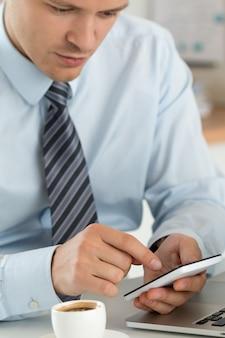 Close-up vista das mãos do empresário segurando um telefone inteligente. aplicativos móveis, jogos, mídia social, organização de trabalho, banco on-line ou conceito de compra.