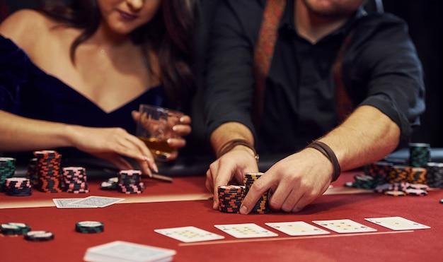 Close-up vista das mãos dos jovens elegantes que jogar poker no casino