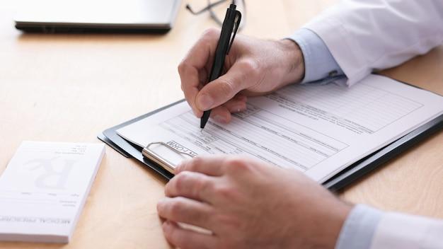 Close-up vista das mãos masculinas dos médicos, escrevendo dados do paciente em formulário médico no consultório médico.