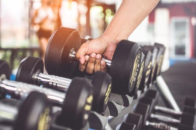 Close-up vista das mãos pegando halteres no rack no ginásio