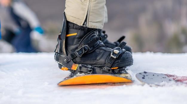 Close-up vista das pernas com botas no snowboard do lado de fora