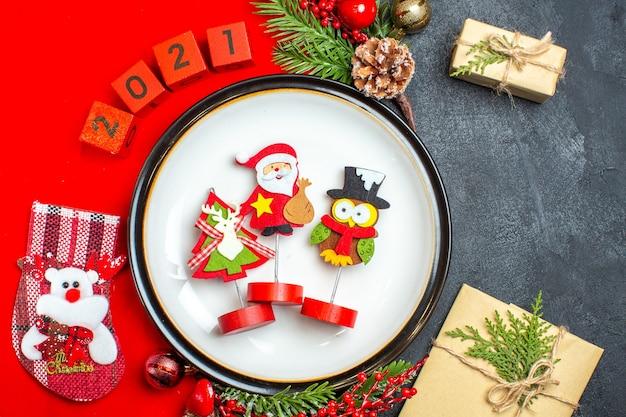 Close-up vista de acessórios de decoração de prato de jantar ramos de abeto e números de meia de natal em um guardanapo vermelho ao lado do presente em uma mesa preta