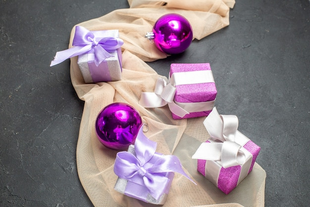 Close-up vista de acessórios de decoração de presentes coloridos para o ano novo em toalha de cor nude em fundo preto