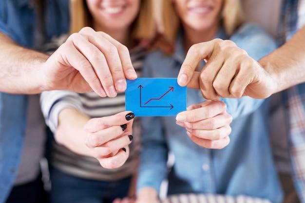 Close-up vista de alegres colegas de trabalho segurando um pequeno papel azul com gráfico crescente.